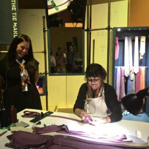 A lady hand stitching a silk tie