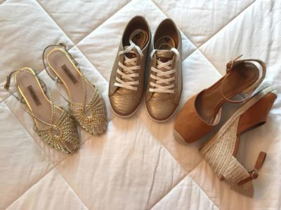 Step three of the travel packing capsule wardrobe is to add three pairs of shoes. Image shows a pair of sneakers, espadrilles and flat heeled, brushed gold sandals.