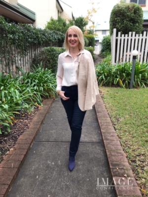 Woman wears a ivory coloured Zara blouse with navy Betty Barclay jeans.