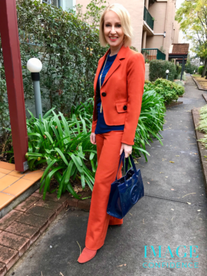 Woman wearing an orange suit and blue top stands near a garden.