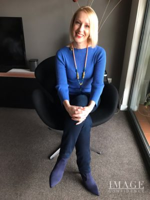 Woman sitting in a chair wears an outfit in various shades of blue