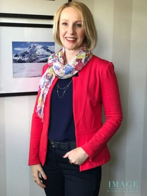 Women wears deep blue top and jeans, coral jacket and multi-coloured scarf.