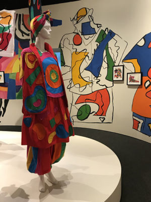 Mannequin wears an bright, bold outfit featuring large rounded shapes.