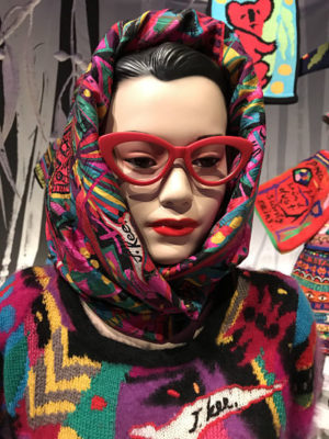 Jenny Kee mannequin wears her iconic red glasses and densely patterned scarf and jumper.