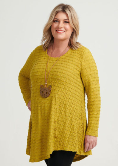 Woman wears long, golden yellow top with a necklace that sits below her bust and on her belly.
