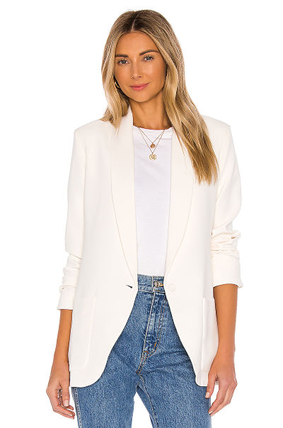 Woman wears white jacket and tee with light blue jeans.