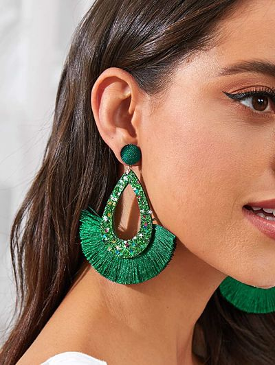 Woman wearing green sparkly earrings.