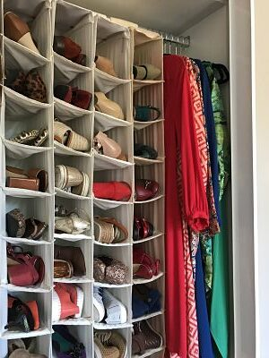 Closet organisation tip: Store shoes in hanging shoe pockets in your wardrobe. Image of many colourful pairs of shoes housed in shoe pockets.