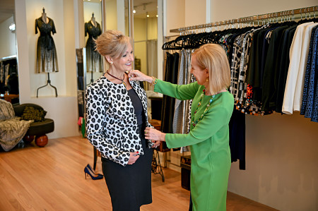 Two women shopping for clothes in a fashion boutique. The personal stylist is helping the other woman select a jacket.