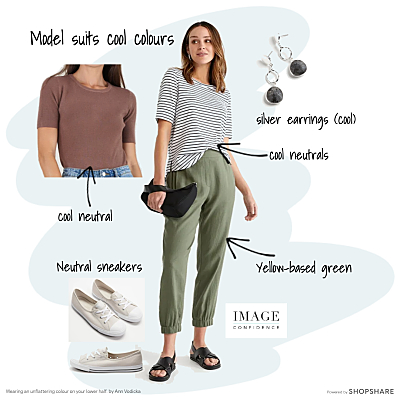 Woman wears a casual outfit of khaki coloured pants, a striped tee shirt, sneakers and silver earrings.